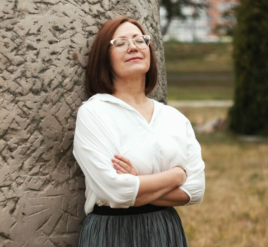 Middle aged woman relaxing against a pillar